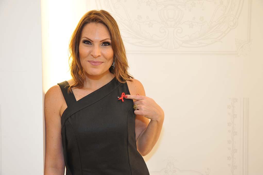 Laura Muller aponta para o laço vermelho, símbolo da Luta Contra a Aids